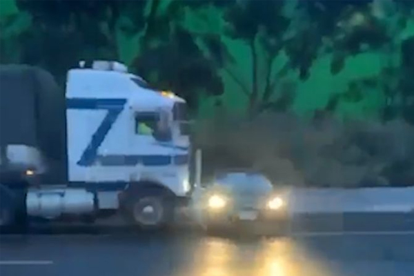 Article image for WATCH | Truck pushes car along wet freeway