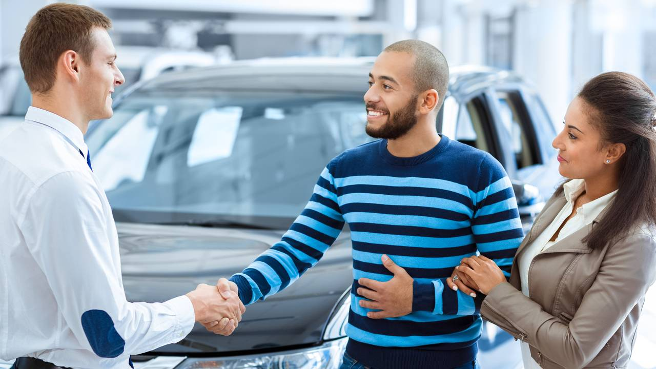 couple-buying-new-car-shaking-hands-with-salesman-at-car-dealership