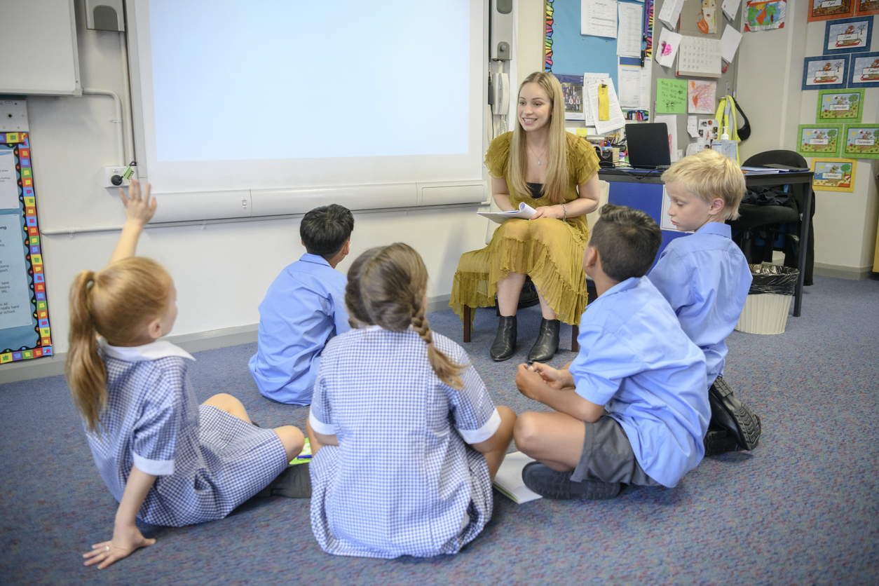 Young woman teaching multi racial students in primary school on the carpet